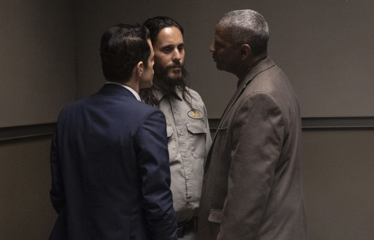 In an interrogation room, Rami Malek in a blue suit and Denzel Washington in a brown suit stand up in the face of Jared Leto who looks like Charles Manson in The Little Things